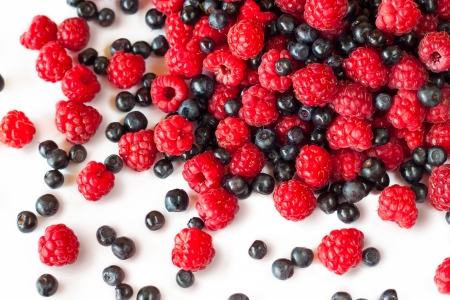 a mixture of raspberries and blueberries on white photo