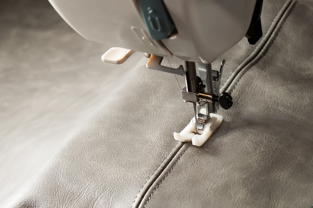sewing machine needle and gray  leather with seam