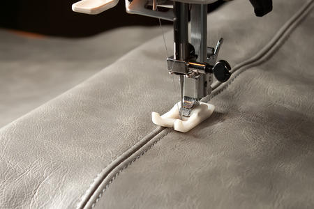sewing machine needle and gray  leather with seam photo