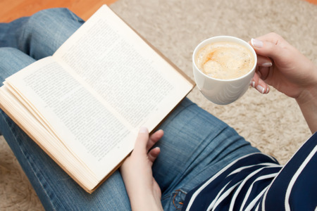 woman reading a book while sitting on the floor and holds cup of coffee Stockfoto