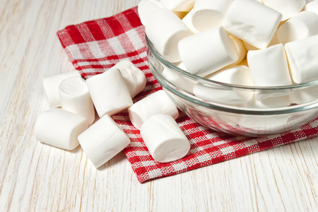 antique table: marshmallow on a plate on a white antique table