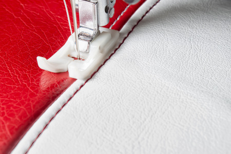 sewing machine and white and red leather with a seam close-up Stockfoto
