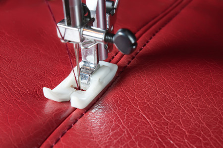 sewing machine and red leather with a seam close-up Archivio Fotografico