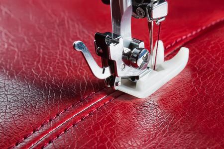 coser: máquina de coser y de cuero rojo con un primer plano de costura Foto de archivo