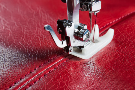 sewing machine and red leather with a seam close-up Stock Photo
