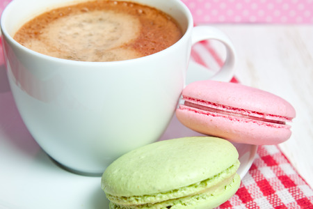 Macaroons and one white cup of coffee photo