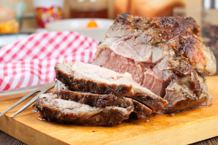 baked meat: grilled meat sliced with spices on a cutting board in the kitchen background