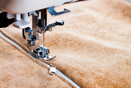 sewing a white zipper on a sewing machine. sewing process