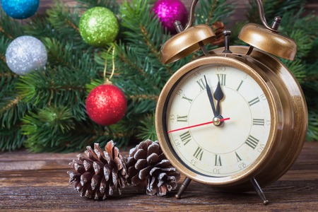 12 month old: New Year clock and fir  branch of Christmas tree decorated with colored balls. Stock Photo
