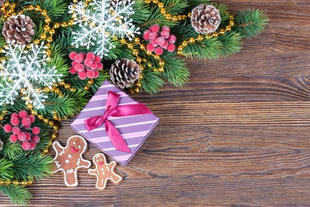 top of the year: Christmas background. Cookies in the shape of man with icing decoration and a present box on brown wooden table. Top view
