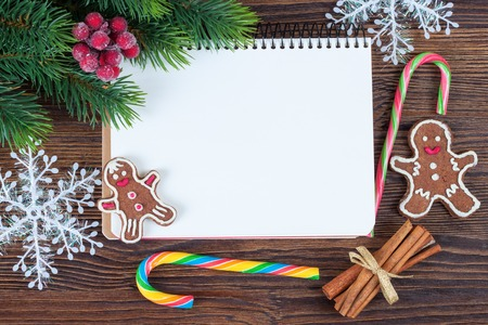 top of the year: Christmas and New Year background with empty note on brown wooden surface. Top view.