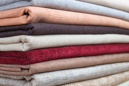 soft sell: Pile of colorful folded textile. Heap of cloth fabric