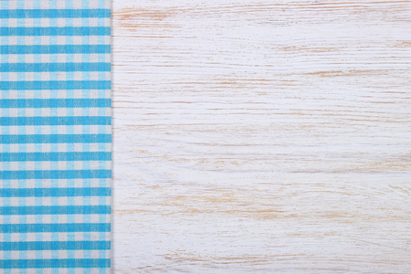 blue white kitchen: Blue checkered tablecloth textile on white wooden table background