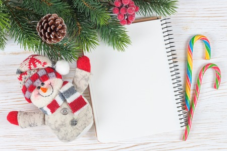 blank note: Christmas and New Year background with empty note on white wooden surface. Top view.