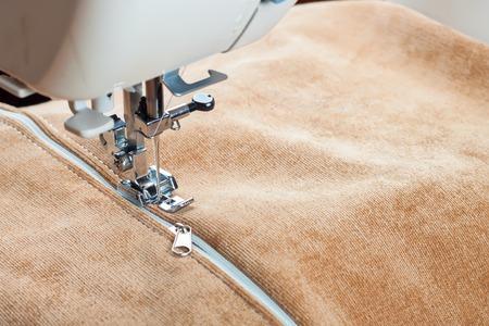 maquinas de coser: coser un cierre de cremallera blanco en una máquina de coser. proceso de costura