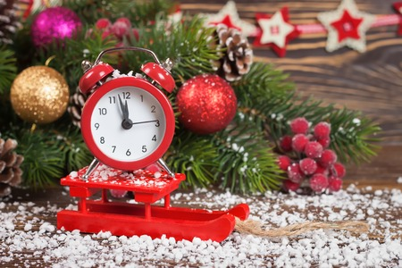 12 days of christmas: Alarm clock on little sledge with snow and Christmas tree on table on brown wooden background