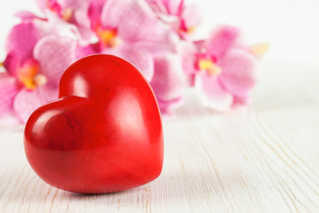 Valentine's day red stone heart and flowers on white wooden background