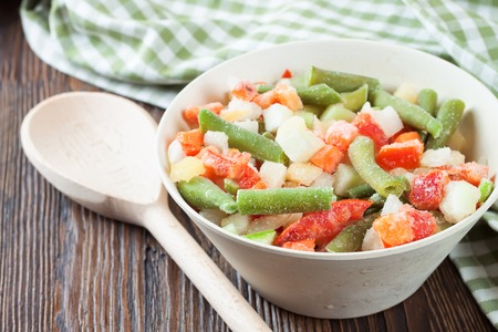 A mixture of assorted frozen vegetables in a bowl on brown wooden table Stockfoto