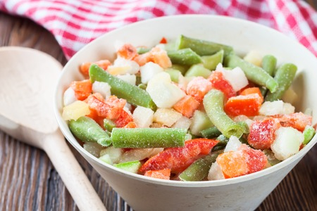 A mixture of assorted frozen vegetables in a bowl on brown wooden table Stock Photo