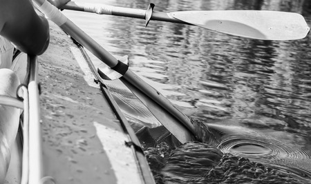 black white kayak: Two retro kayak paddle in the river. Black and white filtered