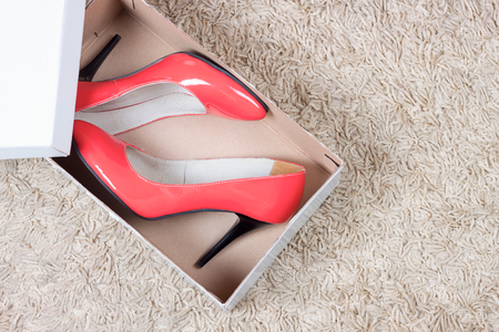 Beautiful  red classic women shoes on high heels in a box on the floor with carpet