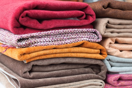 velours: Pile of folded colorful textile. Heap of cloth fabric Stock Photo