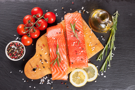 cutting: Raw salmon fillet and ingredients for cooking on a cutting board and  dark  slate background. Top view Stock Photo
