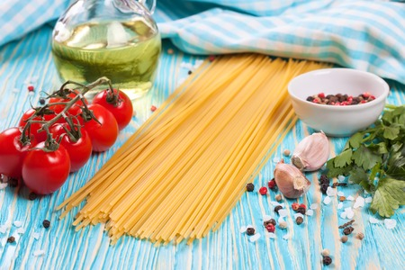 ingridients: Pasta ingridients, blue checkered towel and spice on blue wooden surface. Stock Photo