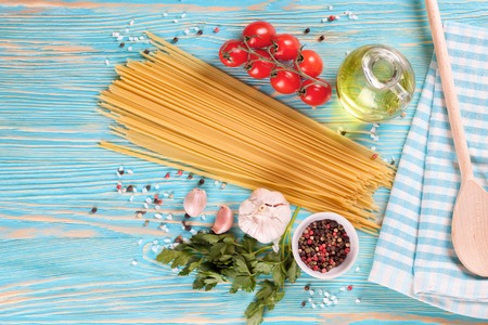 ingridients: Pasta ingridients and spice on blue wooden surface. Top view. Stock Photo