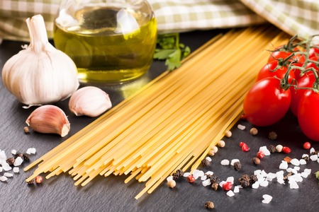 ingridients: Pasta ingridients and spice on black slate surface. Top view. Stock Photo