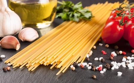 ingridients: Pasta ingridients and spice on black slate surface.