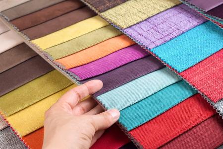 La donna sceglie i campioni di tessuto colorato sul tavolo vicino