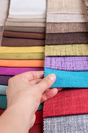 chooses: Woman chooses samples of colored fabric on table close up