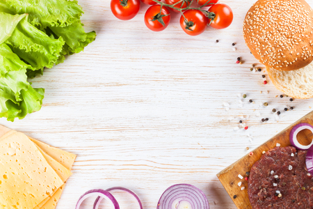 The raw ingredients for the homemade burger on white wooden table. Top view. Stock Photo