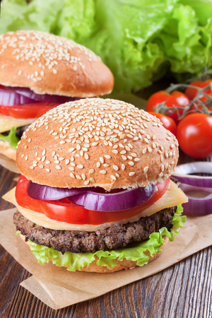 cheeseburgers: Two homemade cheeseburgers with beef patties , fresh salad, tomatoes and onion on seasame buns, served on brown wooden table.