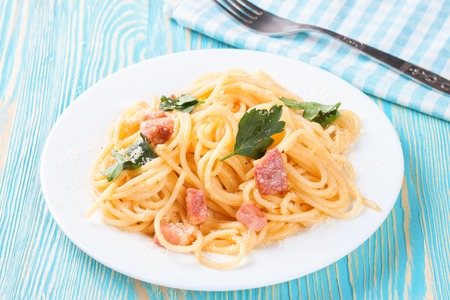 Pasta Carbonara with ham and cheese on blue wooden suface. Top view. Stock Photo