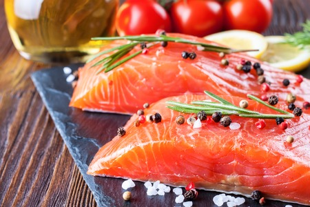 brown trout: Raw salmon fillet and ingredients for cooking on a slade board and brown wooden background. Stock Photo