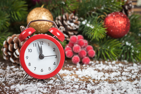 New Year clock and fir branch with red rowan, snow, balls and decoration on brown wooden background