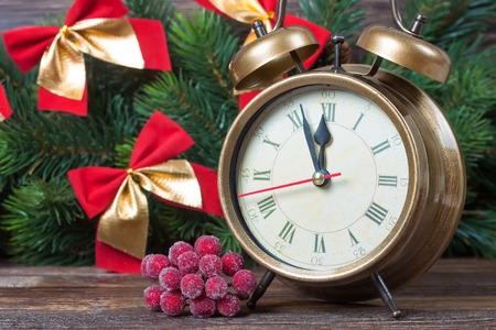 New Year clock and fir branch of Christmas tree decorated with red bows.