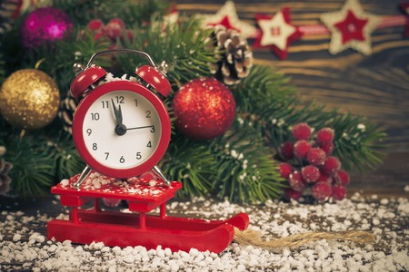Alarm clock on little sledge with snow and Christmas tree on table on brown wooden background. Filtered in warm tone.