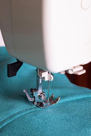 Close-up van naaimachine met turquoise stof Stockfoto