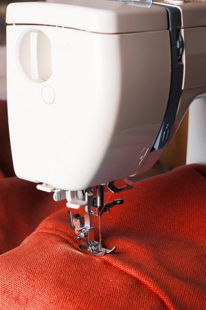 sewing machines: Close up of sewing machine working with red fabric Stock Photo