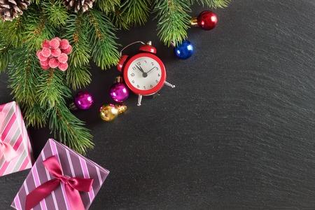 Nieuwjaar achtergrond met kerstboom en geschenkdoos op zwarte leisteen oppervlak. Bovenaanzicht.