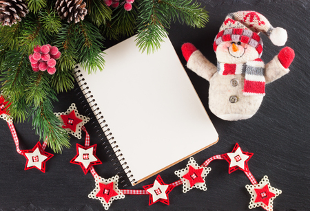 New Year background with Christmas tree, toy snowman and empty note greeting card on black slate surface. Top view.