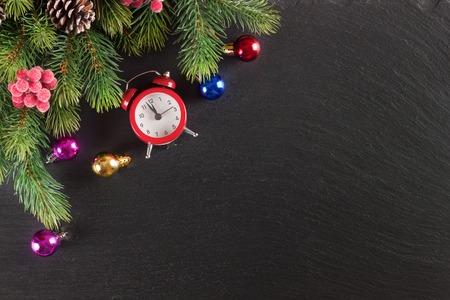 Nieuwjaarachtergrond met Kerstboom en decoratie op zwarte leioppervlakte. Bovenaanzicht.