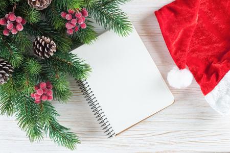 Nieuwjaar achtergrond met kerstboom en lege notitie wenskaart op witte houten oppervlak. Bovenaanzicht. Stockfoto - 91278426