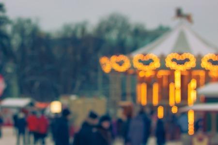 Kleurrijke bokeh defocused carrousel bij de eerlijke lichten van Kerstmis. Onscherpe achtergrond Nieuwjaarsbeurs. Gefilterd in vintage stijl. Stockfoto