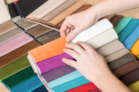 Man chooses samples of colored fabric on table close up Stockfoto - 97848331
