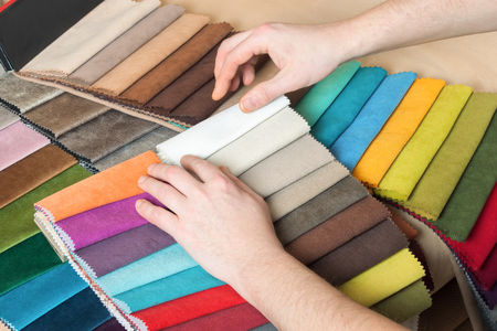 Man chooses samples of colored fabric on table close up Stockfoto - 104872269