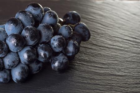 fresh ripe black grapes on dark slate background, top view. Stockfoto - 99029309
